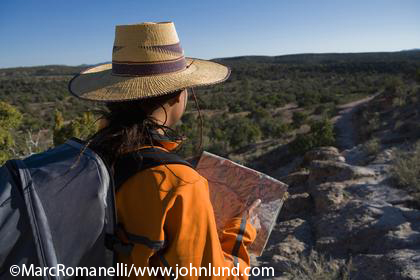 Picture of a black woman with a map in her hands hiking on a trail in the wilderness